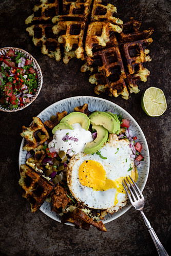 Fried egg with avocado and potato waffles