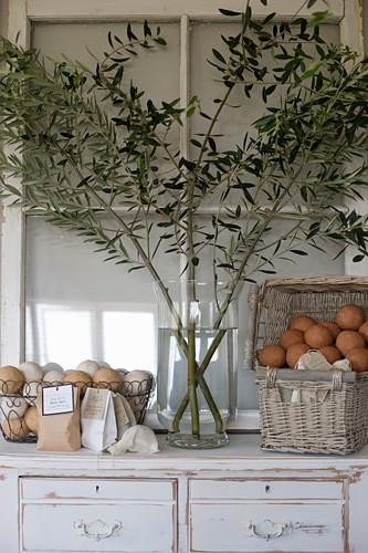 Olivenzweige in einer Vase und Körbe mit Badekugeln