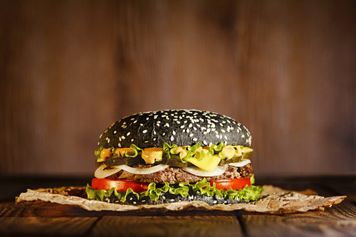 Black burger on paper on a dark background