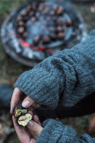 A woman breaking apart a roasted chestnut