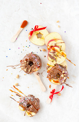 Caramelized Apple Slices on a Sticks with Nuts and Colored Sprinkles