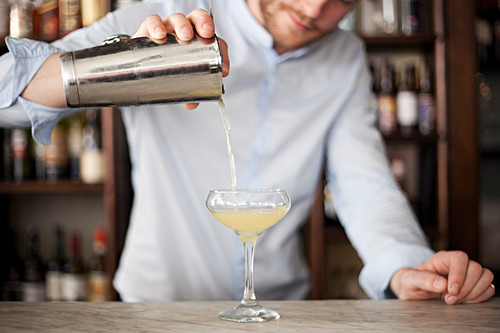 A barman pouring a cocktail