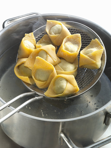 Fresh tortellini in a sieve with a pan of boiling water