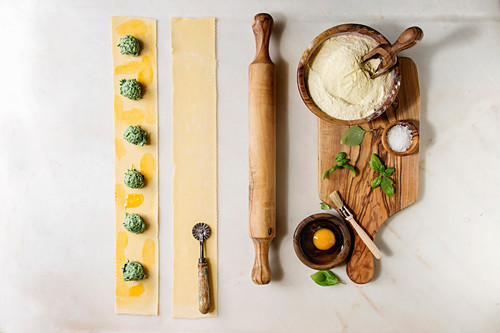 Ingredients for homemade italian pasta ravioli staffed by spinach ricotta, semolina flour, egg yolk, basil, olive wood utensils bowls, scoop and rolling pin