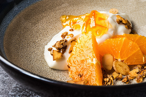 Orange dessert with yoghurt and roasted almonds