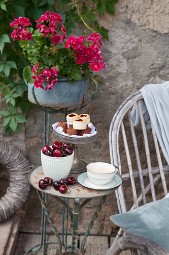 Bowl of cherries, coffee cup and pastries on cake stand on small vintage table on terrace
