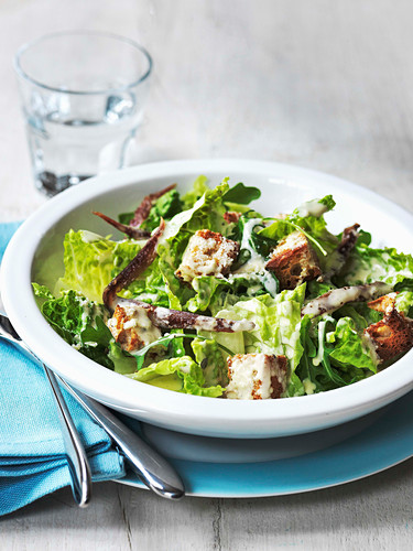 Caesar salad with Romaine lettuce rocket anchovies and croutons with a parmesan cheese dressing
