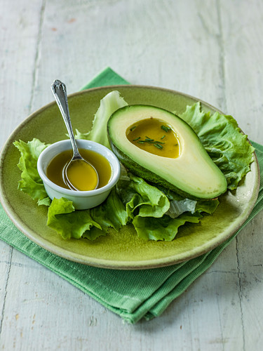 Avocado with vinaigrette dressing and chives ona bed of lettuce
