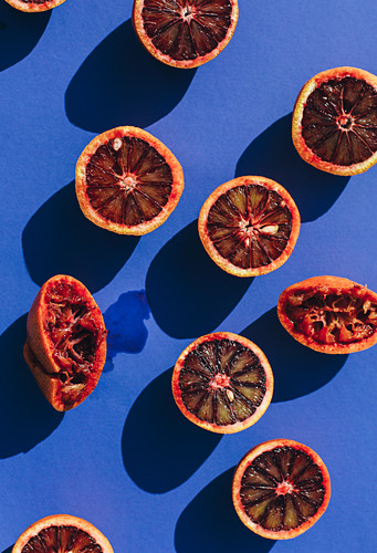 Halved blood oranges throwing a shadow on a blue background