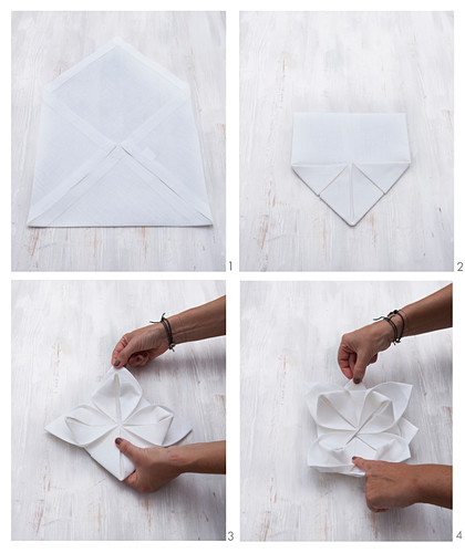 A fabric napkin being folded into a flower