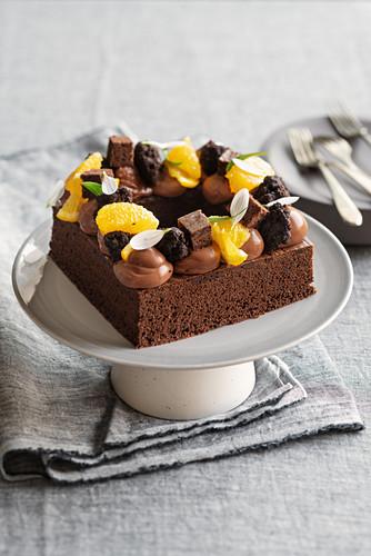 Quadratischer Sacherkuchen mit schwarzen Schoko-Trüffeln, Schokoladencreme und Orange