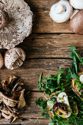 Different kind of mushrooms and ruccola on a wooden background