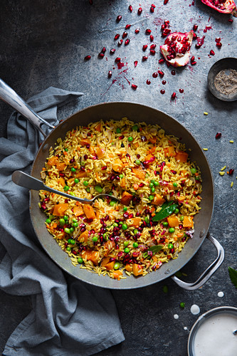 Vegeterian dish of pilaf rice with roasted butternut squash, peas, spices (cumin, tumeric) and pomegranate