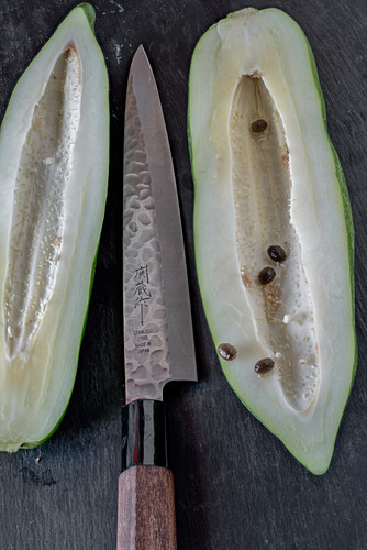 Halved, young papaya with a knife on a black surface