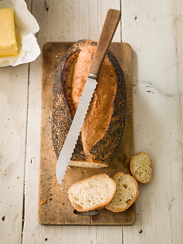 Poppy Seed loaf sliced with butter and knife