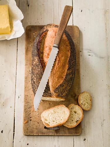 Mohnbrot, angeschnitten, mit Butter und Messer