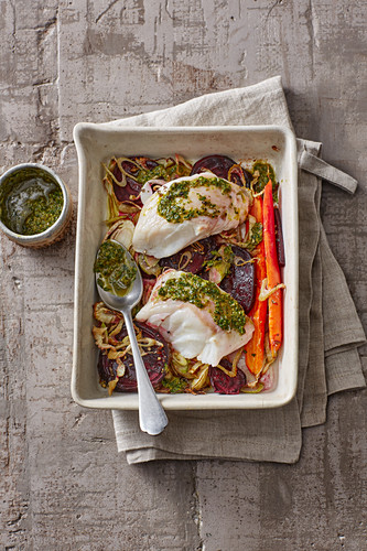 Cod on a bed of vegetables with pesto
