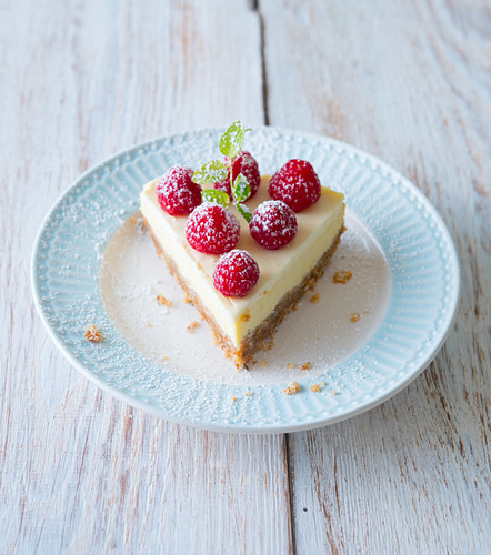 A slice of raspberry cheesecake garnished with mint