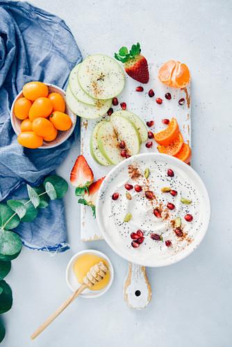 Yogurt fruit dip garnished with poppy seeds, pomegranate arils, pistachios and cinnamon .