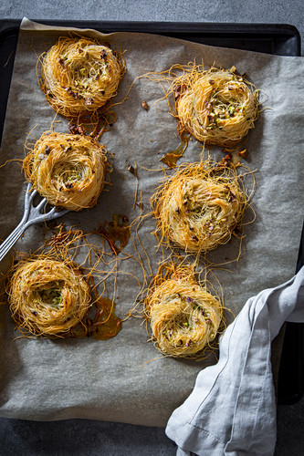 Angel hair pasta nests with pistachios on a baking tray with baking paper and a vintage spatula