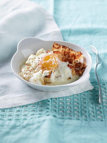 Slow-cooked egg on croutons with cheese and crispy bacon