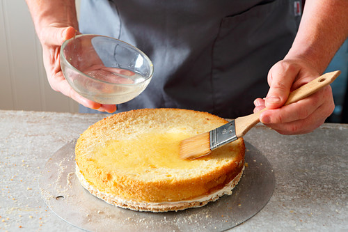 Swiss Zug cherry cake being made: a sponge base being brushed with liquid