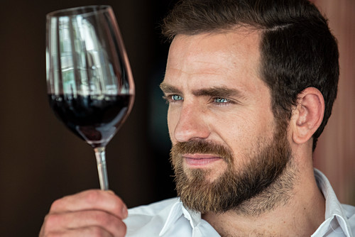 Mid adult man looking at wine glass