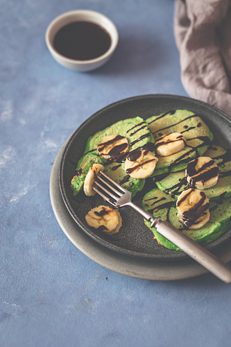Green spinach pancakes with banana slicces and chocolate sauce