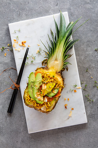 A pineapple bowl with oriental noodles, vegetables and avocado in a fresh pineapple on a white marble platter