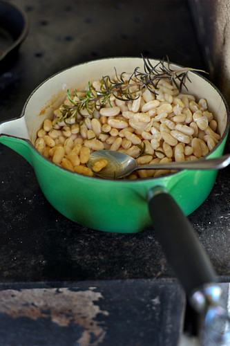 A pan of beans with rosemary on a hot plate