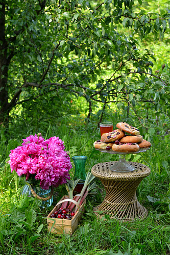 A stack of yeast dough pastries with cherries on a cake stand next to a large bouquet of flowers in a vase