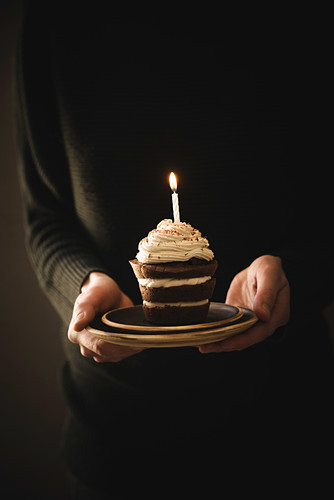 A woman holding a vegan cream cake with a burning candle