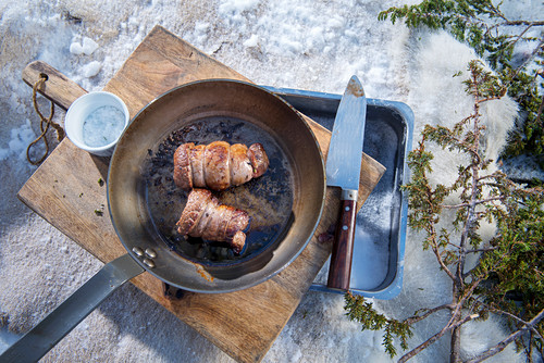 A winter barbecue: elk roulade in a pan in the snow (Norway)