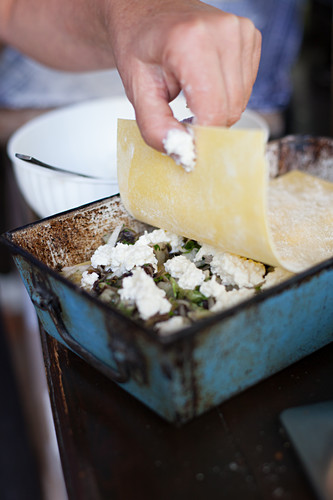 Lasagne with radicchio and asiago cheese being layered in a baking dish
