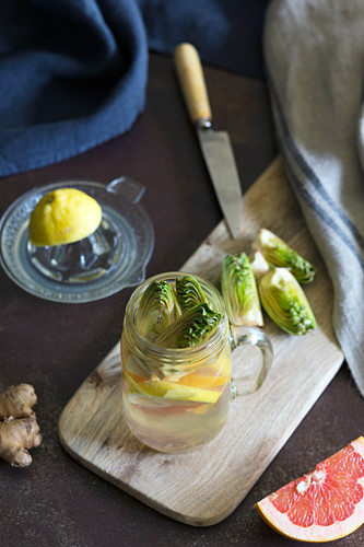 Jar of fresh citrus beverage with fresh artichoke and ginger placed on wooden board