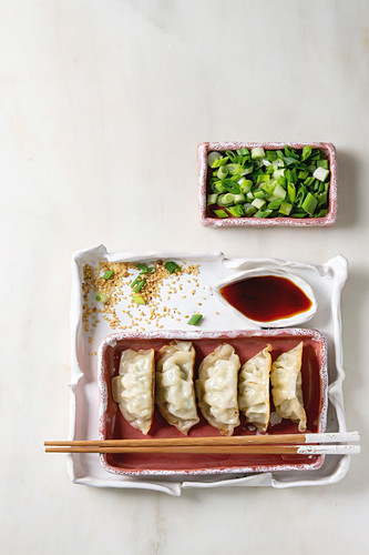 Fried asian dumplings Gyozas potstickers in pink square ceramic plate with chopsticks, bowl of soy sauce and chopped spring onion