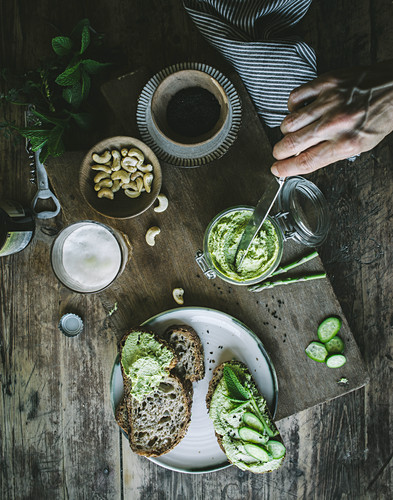 From above hand of unrecognizable person cook making toasts with green cashew pate and slices of cucumber on wooden board
