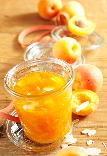 Apricot jam with almond liqueur on a wooden surface