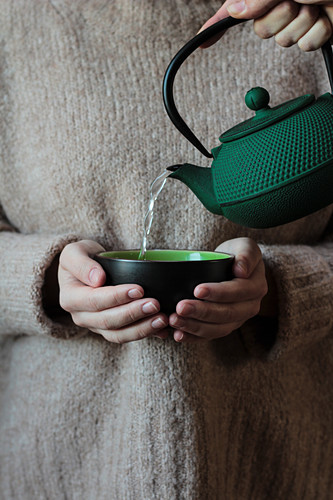 Green black cup in hands of woman in sweater and teapot with pouring water
