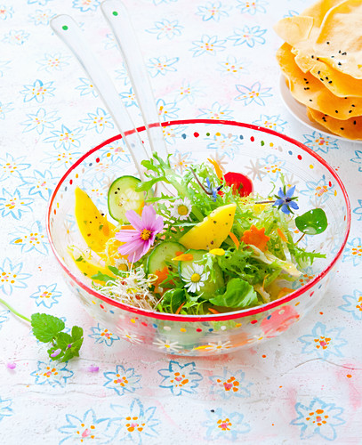 A salad with flowers in a glass bowl