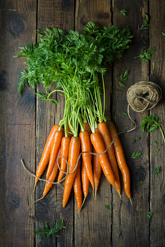 A bundle of freshly washed carrots with green tops on a wooden surface