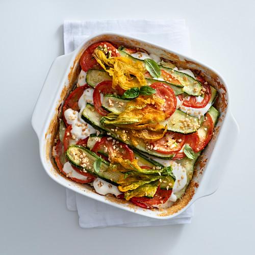 Zucchini bake with mozzarella, tomatoes and zucchini flowers