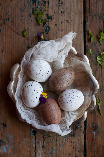 Speckled eggs on piece of muslin in rustic bowl