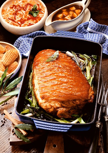 Roast pork with crackling in roasting dish, gravy in sauceboat