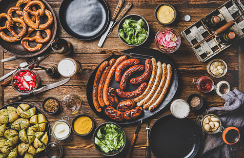 Octoberfest dinner table concept with grilled meat sausages, German pretzel pastry, potatoes, cucumber salad, sauces, beers in bottles and glasses