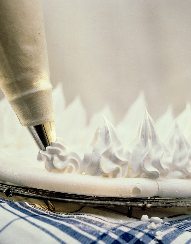 Piping meringue rosettes on meringue base with icing pipe