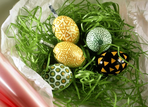 Colourful Easter eggs & banknote rolls in artificial grass