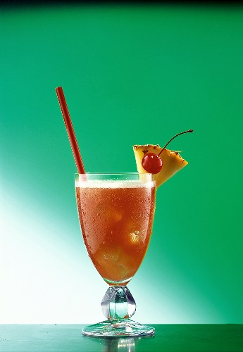 A glass of Planter's Punch with straw, pineapple, cherry