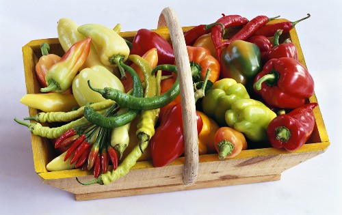 Various types of peppers & chili peppers in wooden basket