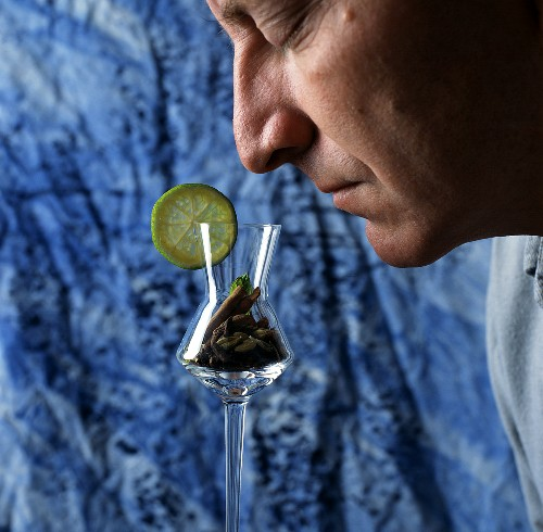 Man smelling schnapps flavours in glass (filled with spices)